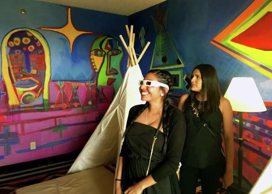 Kalene Thompson, left, views an installation art piece by contemporary Native American artist Ishkoten Dougi through 3-D glasses at the Nativo Lodge in Albuquerque, N.M.  Nativo Lodge has transform 12 guest rooms in recent years into spaces that owners say can be considered art pieces unto themselves.  Photo: Mary Hudetz, STF / Copyright 2016 The Associated Press. All rights reserved. This material may not be published, broadcast, rewritten or redistribu