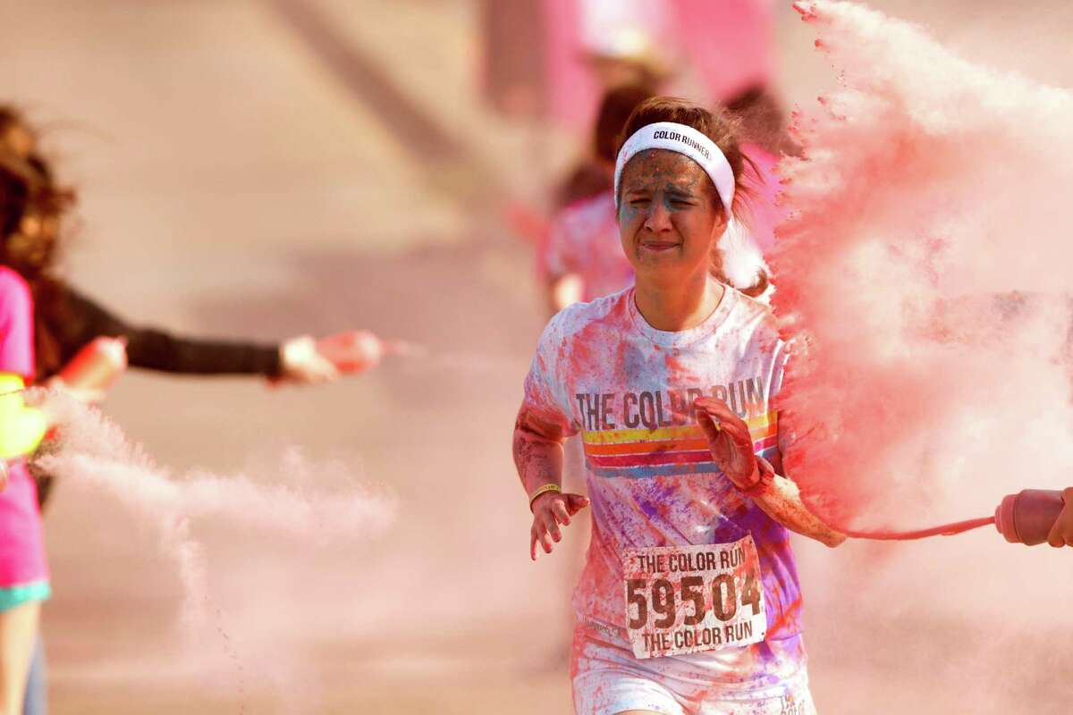 Runners are sprayed with colored cornstarch in the pink zone during Color Run Houston 5K.
