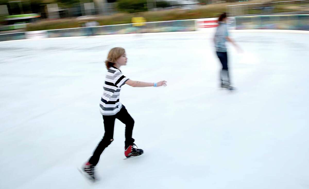 Adults and children skate around Discovery Green Ice Rink.