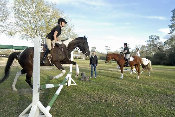 """With Kendall Sill (15-year-old 9th grader at Episcopal H.S) jumping with """"Otto"""" at left - Merrily Quincoces offers riding lessons at the Houston Polo Club Wednesday 2/27/13. At right is Cristina Jordan (13-year-old 7th grader at Spring Branch Middle School) atop """"Hanna"""" and behind her is Gavi Silverman (14-year-old 8th grader at Awty International School) atop """"Toby"""". Photo by Tony Bullard."""
