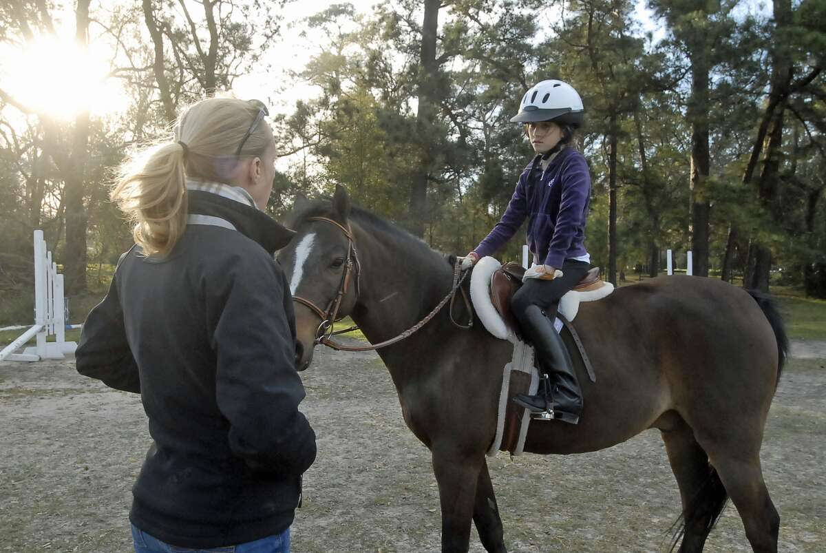 """Merrily Quincoces offers riding lessons to Hallie Grimes (10-year-old 5th grader at Post Oak Montessori) atop """"Winston"""" at the Houston Polo Club Wednesday 2/27/13. Photo by Tony Bullard."""