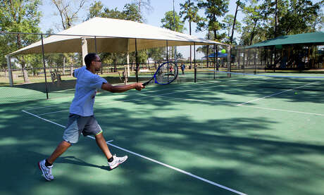 Michael Dixon plays tennis with his son at Crowley Park.