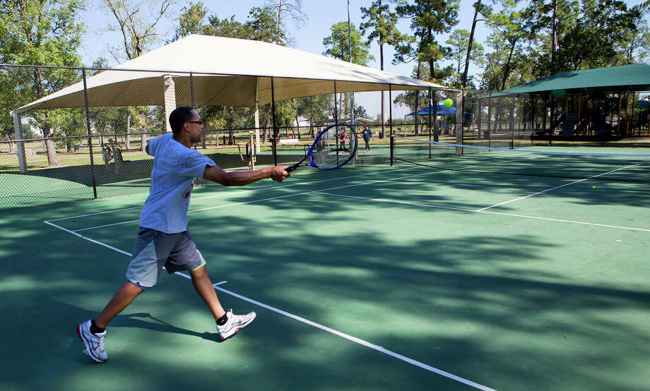 Michael Dixon plays tennis with his son at Crowley Park. Photo: Cody Duty, Staff / © 2015 Houston Chronicle