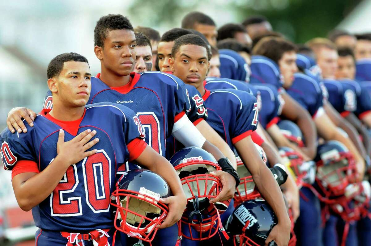 Schenectady running back Felix Rodriguez, left, and quarterback Kwame Jarvis join the team during the playing of the National Anthem before their football game against Columbia on Friday, Aug. 31, 2012, at Schenectady High in Schenectady, N.Y. The state Senate on Tuesday by a 58-0-margin approved a measure that would prevent cities from requiring a permit before singing of the National Anthem or reciting the Pledge of Allegiance. (Cindy Schultz / Times Union archive)