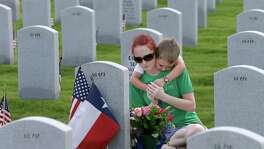 Kristin Segura is hugged by her four-year-old son, Xavier Segura, as she sits by the grave of her husband and his father, Alexander G. Segura III, on Memorial Day at the Houston National Cemetery, 10410 Veterans Memorial Drive, Monday, May 25, 2015, in Houston. Alex Segura was born July 1, 1984 and died August 6, 2012 after being shot by an assailant in Houston.  He served in Iraq as a Lance Corporal in the Marines, Echo Company, Second Battalion.