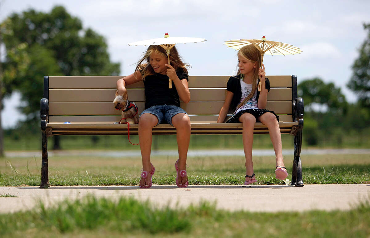Camila Alvares, left, of Katy sits on a park bench with her dog, Cloe, a Yorkshire Terrier and friend Juliana Wilson, at Millie Bush Dog Park in George Bush Park.