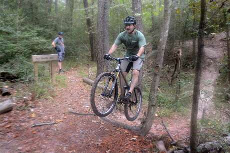 Bill Collier watches as Mitch Callihan, both of Cypress, jumps an obstacle, after riding through a creek on the bike trails at the 100 Acre Wood Preserve, 10602 Normont. The preserve has 2 miles of trails through rolling, forested terrain. Photograph by David Hopper