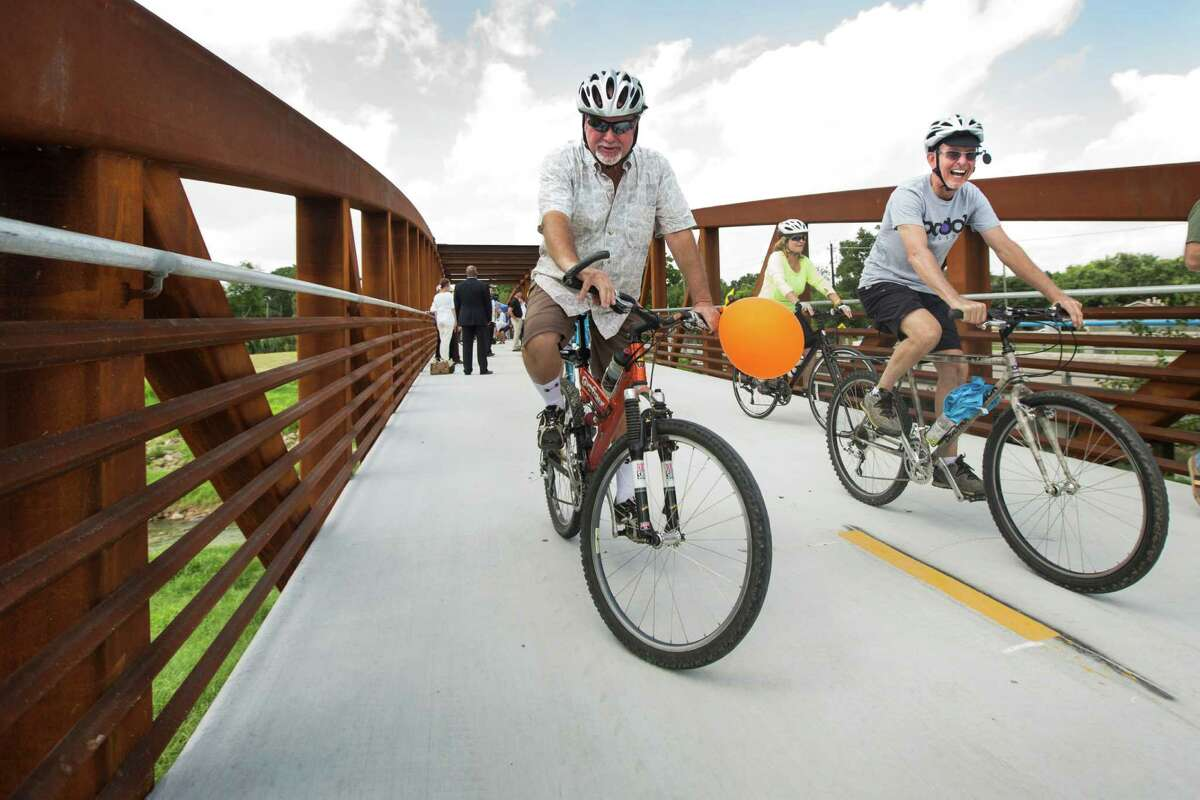 Dwight Dawson, left, and John Youens ride across a new bridge during the official opening of White Oak Bayou Path on Thursday, July 9, 2015, in Houston. The Houston Parks and Recreation Department opened the new hike and bike trail from Alabonson Road to Antoine Drive Link. The ceremony marks the completion of the first of six TIGER (Transportation Investment Generating Economic Recovery) grant-funded projects. ( Brett Coomer / Houston Chronicle )