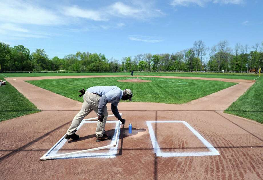 """Oscar Miranda, head of maintenance for Brunswick School and his assistant, Duke Moss, pictured here removing the template for the batter's box he sprayed in, worked as the grounds crew as they prepared the Brunswick School baeball field for the game between Brunswick School and Hopkins School at Brunswick in Greenwich, Conn., Wednesday, May 11, 2016. """"It is more art than craft,"""" said Moss about the hour-plus long process of making sure the field comes out looking perfect. """"We love what we do,"""" said Miranda after using white line spray to lay-down the first base line, one of the last things done in the process. """"The hard part is when it rains, sometimes after it rains it takes a few hours to get a rainy field ready. We go through a lot of speed-dry on a rainy field,"""" said Moss. Brunswick School took advantage of their well-prepared field as they beat Hopkins School 7-5 as Charlie Sealy pitched the home team to victory. Photo: Bob Luckey Jr. / Hearst Connecticut Media / Greenwich Time"""