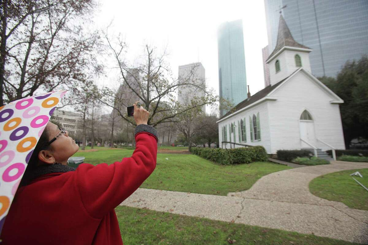 Ledys Garcia, student at Lee Collage from Baytown, photographs St. John Church, 1891, and the downtown skyline during a tour of The Heritage Society at Sam Houston Park on Friday, Feb. 17, 2012, in Houston. ( Mayra Beltran / Houston Chronicle )