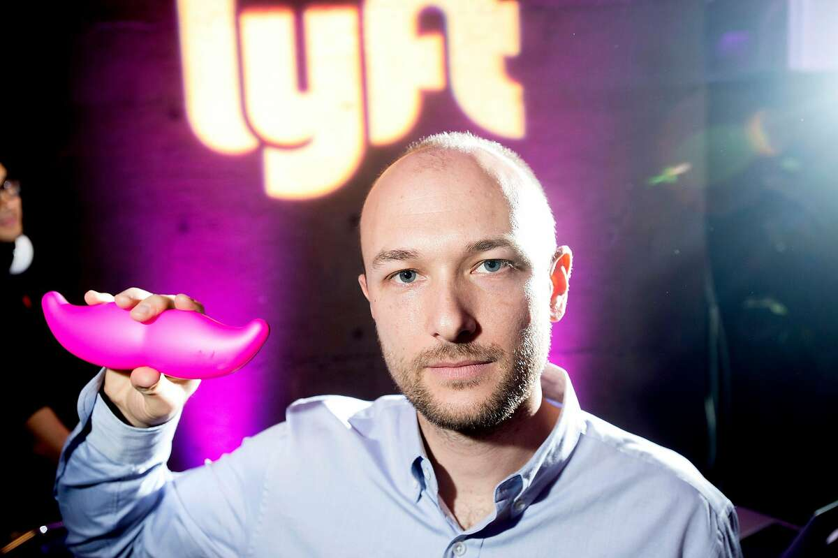 """FILE - In this Monday, Jan. 26, 2015, file photo, Logan Green, co-founder and chief executive officer of Lyft, displays his company's """"glowstache"""" during a launch event in San Francisco. On Monday, Jan. 4, 2016, General Motors Co. announced it is investing $500 million in ride-sharing company Lyft Inc. GM gets a seat on Lyft's board as part of the partnership, which could speed the development of on-demand, self-driving cars. (AP Photo/Noah Berger, File)"""