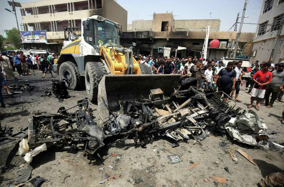 A bulldozer clears the wreckage following a car bomb attack Wednesday in Sadr City, a Shiite area north of the capital Baghdad. Photo: AHMAD AL-RUBAYE, Stringer / AFP or licensors