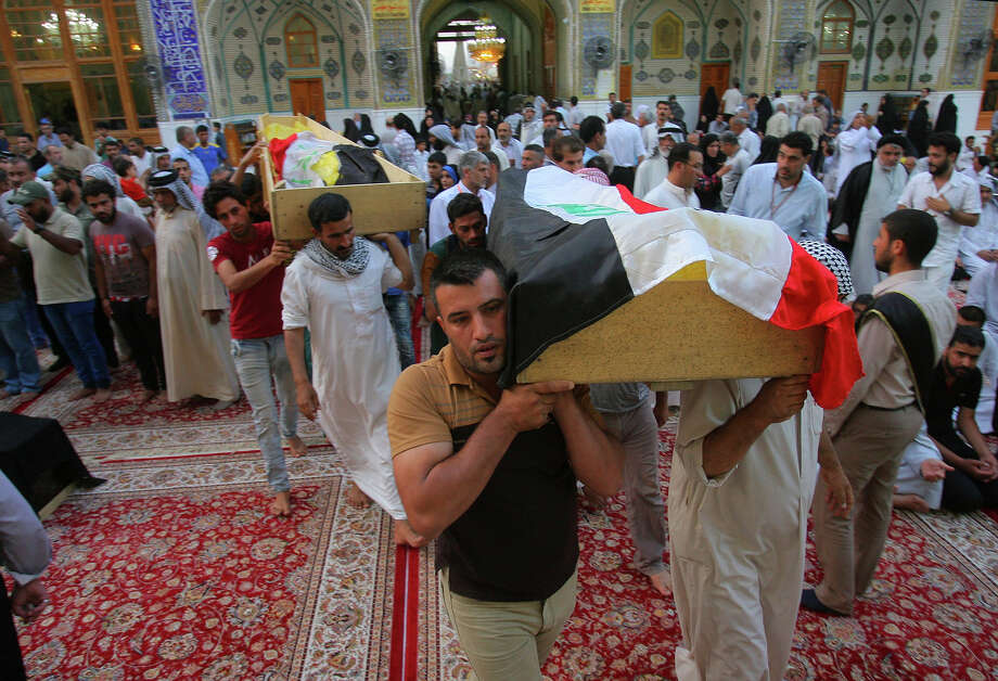 Mourners carry the flag-draped coffins of Baghdad bomb victims Zakia Kadim, 38, and her son Mohammed Jassim, 11, during their funeral procession at the holy shrine of Imam Ali in Najaf, Iraq. Photo: Anmar Khalil / Associated Press / AP