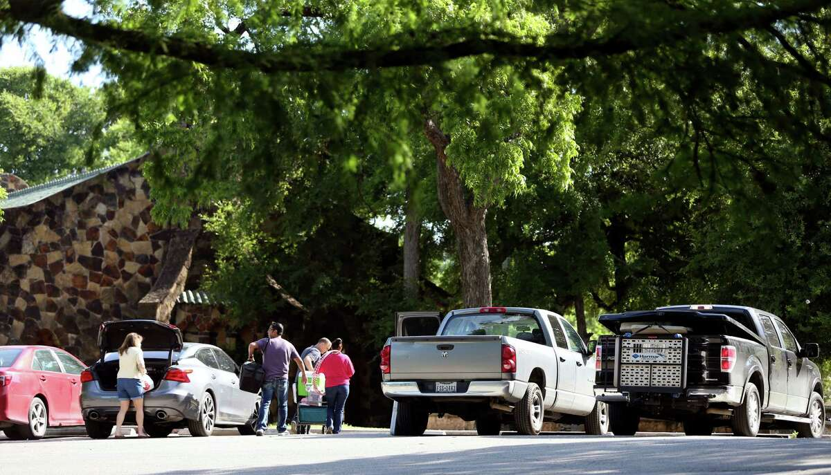 """People unload their cars in Brackenridge Park. One park visitor said, """"I've never heard of parking in a garage, then going to a park."""""""