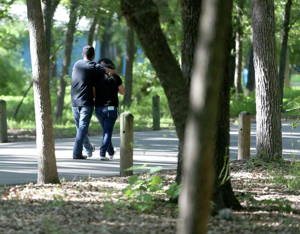 Two people walk together Wednesday morning, May 4, 2016 through Brackenridge Park.