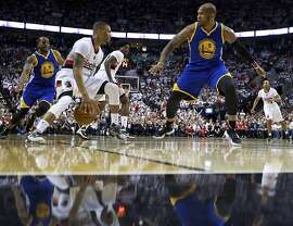 Portland Trail Blazers guard Damian Lillard, center, dribbles past Golden State Warriors center Marreese Speights, right, and forward Andre Iguodala, left, during the second half of Game 4 of an NBA basketball second-round playoff series Monday, May 9, 2016, in Portland, Ore. The Warriors won 132-125. (AP Photo/Craig Mitchelldyer)