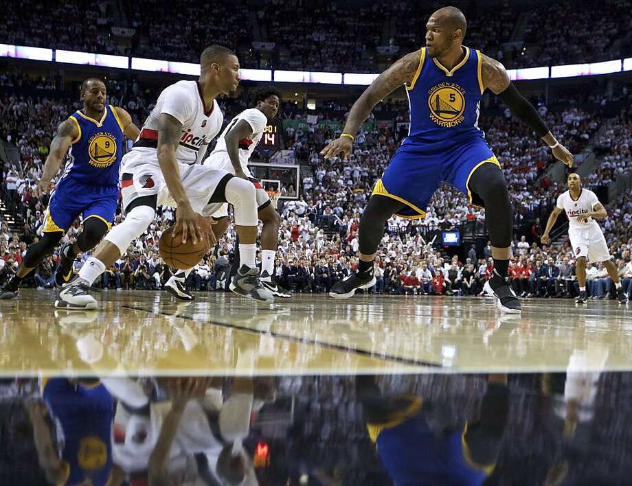 Portland Trail Blazers guard Damian Lillard, center, dribbles past Golden State Warriors center Marreese Speights, right, and forward Andre Iguodala, left, during the second half of Game 4 of an NBA basketball second-round playoff series Monday, May 9, 2016, in Portland, Ore. The Warriors won 132-125. Photo: Craig Mitchelldyer, Associated Press