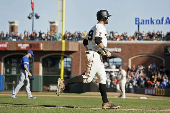 San Francisco Giants' Brandon Belt, right, comes in to score the Giants' game-winning run as Toronto Blue Jays relief pitcher Ryan Tepera, left, walks off the field in the 13th inning of their baseball game Wednesday, May 11, 2016, in San Francisco. San Francisco won the game 5-4. (AP Photo/Eric Risberg)