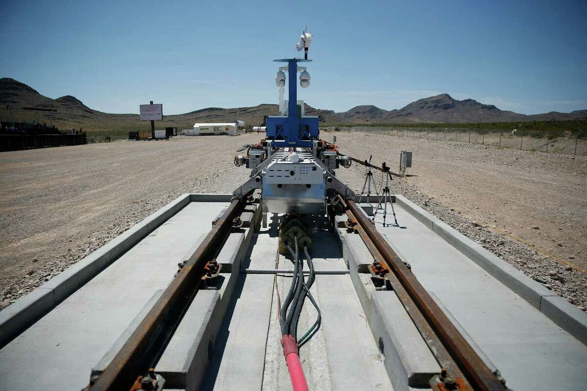 A recovery vehicle and test sled sit on a track after a test of a Hyperloop One propulsion system, Wednesday, May 11, 2016, in North Las Vegas, Nev. The startup company opened its test site outside of Las Vegas for the first public demonstration of technology for a super-speed, tube based transportation system. (AP Photo/John Locher)