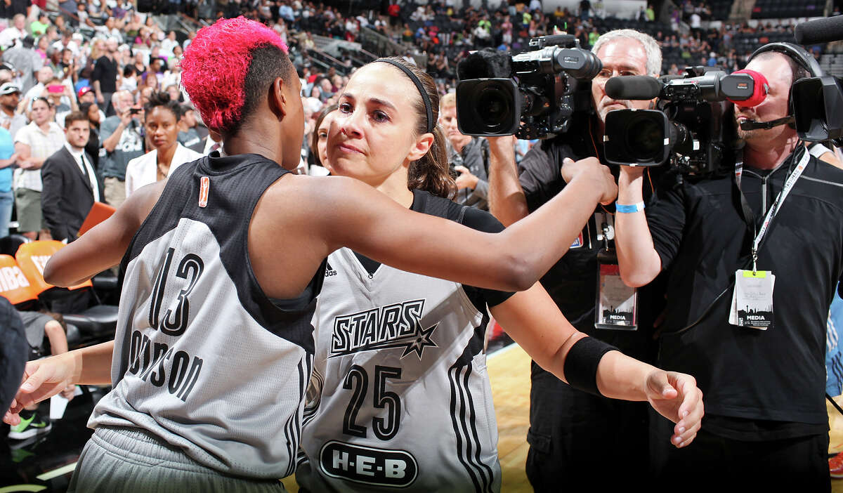Stars' Danielle Robinson (left) hugs teammate Becky Hammon after the game with the Minnesota Lynx on Aug. 23, 2014 at the AT&T Center. Hammon, who is retiring, will become the first woman to serve as a full-time NBA assistant coach with the Spurs.