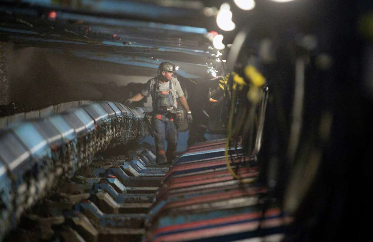 A miner walks under hydraulic jacks next to a coal seam in Williamson Energy's Pond Creek longwall coal mine in Johnson City, Illinois, U.S., on Monday June 21, 2010. Photographer: Andrew Harrer/Bloomberg