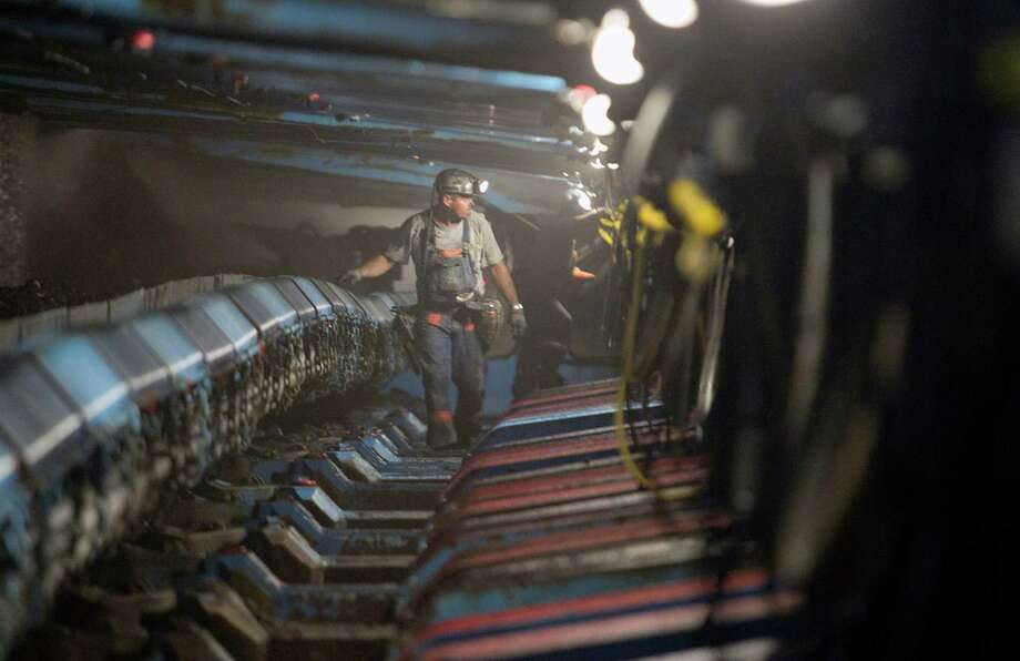 A miner walks under hydraulic jacks next to a coal seam in Williamson Energy's Pond Creek longwall coal mine in Johnson City, Illinois, U.S., on Monday June 21, 2010. Photographer: Andrew Harrer/Bloomberg Photo: Andrew Harrer / © 2010 Bloomberg Finance LP