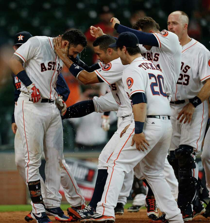 Astros first baseman Marwin Gonzalez, left, is met by a host of happy teammates after breaking a 3-3 tie with a 16th inning home run off the Indians' Cody Anderson. Photo: Karen Warren, Staff / © 2016 Houston Chronicle