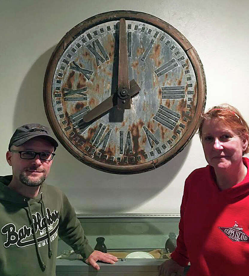 """Thanks to the generosity of Knecht Woodworking, a more than 120-year-old clock has been mounted at the Trumbull Historical Society. Pictured are Brian LaVoie, treasurer, and Jennifer Winschel, board member. The clock, purchased by a tavern owner, was intended for the Trumbull Congregational Church steeple. But church leaders refused to accept the clock because it was bought with funds from a tavern."""" Photo: Trumbull Historical Society /Facebook"""
