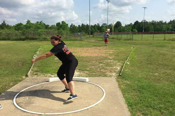 Deweyville's Mallory Dotson practices her shot put while her father, William, who is also the team's throwing coach, watches in the background on Tuesday in preparation for this weekend's state track and field meet in Austin. (Brooks Kubena/The Enterprise)