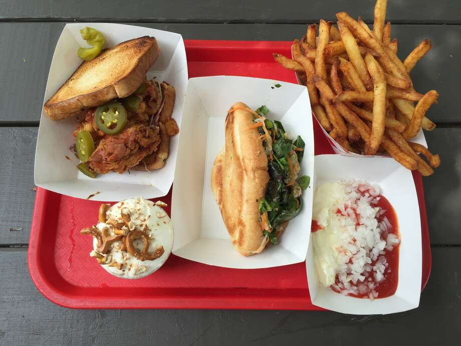 A sample of dishes from The Luxury. From top left: Fried chicken sandwich with spicy slaw, chocolate pudding with crumbled pretzels, crispy fish banh mi, fries, a mix of mayo, mustard and chopped onions.