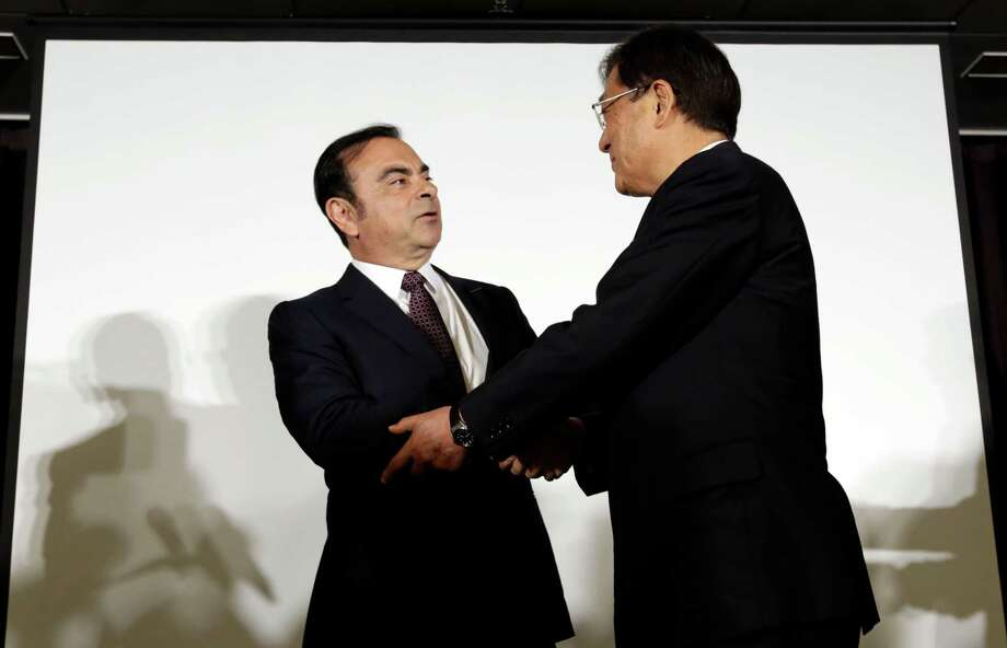 Nissan Motor Co. CEO and President Carlos Ghosn (left) and Mitsubishi Motors Corp. Chairman and CEO Osamu Masuko shake hands after their joint news conference to announce that Nissan is taking a 34 percent stake in scandal-ridden Mitsubishi Motors. Photo: Eugene Hoshiko /Associated Press / Copyright 2016 The Associated Press. All rights reserved. This material may not be published, broadcast, rewritten or redistribu