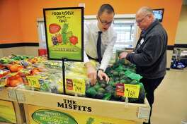 Ryan Merone, left, a Hannaford field produce merchandizer for New York and Vermont and John Benoit, produce manager at the Hannaford on Central Ave., stock a display with misshapen or discolored fruits and vegetables on Tuesday, May 12, 2016, in Albany, N.Y.   (Paul Buckowski / Times Union)