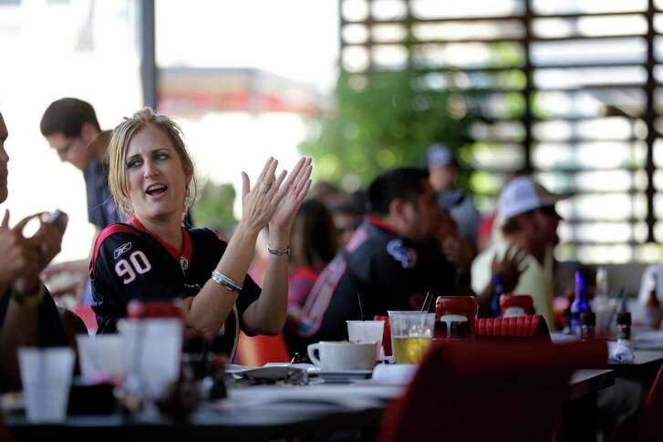 Texans fan, Michelle Rhone, watches the Houston Texans first regular season NFL football game of the season against the Miami Dolphins, Sunday, September 9, 2012 at The Houston Texans Grille in Houston, Texas. (Todd Spoth / For The Chronicle)