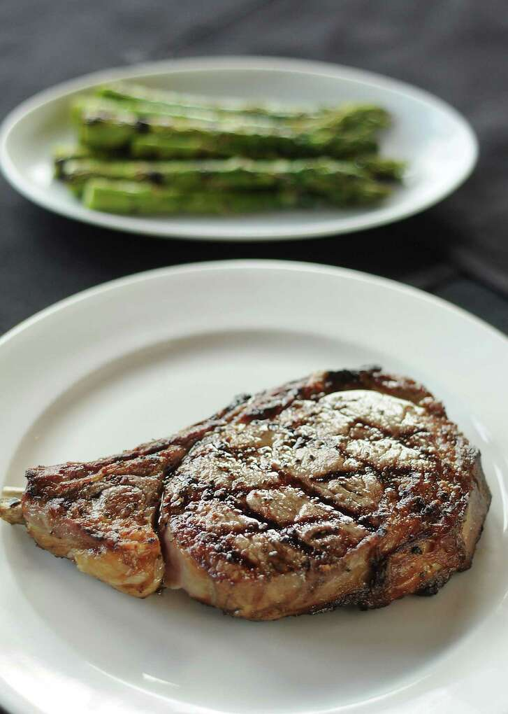 The dry-aged bone-in ribeye with a side of asparagus at B&B Butchers