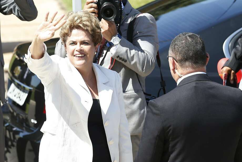 President Dilma Rousseff waves to supporters after the Senate voted to accept impeachment charges. Photo: Igo Estrela, Getty Images