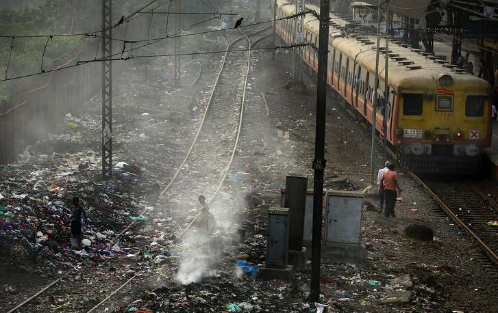 FILE � In this Monday, Jan 26, 2015 file photo, a local train moves past burning garbage at a local train station in Mumbai, India. The World Health Organization on Thursday May 12, 2016 released new information from its Global Urban Ambient Air Pollution Database, that says 98 percent of residents in large cities of low- and middle-income countries are facing excessively high air pollution. (AP Photo/Rafiq Maqbool, File)