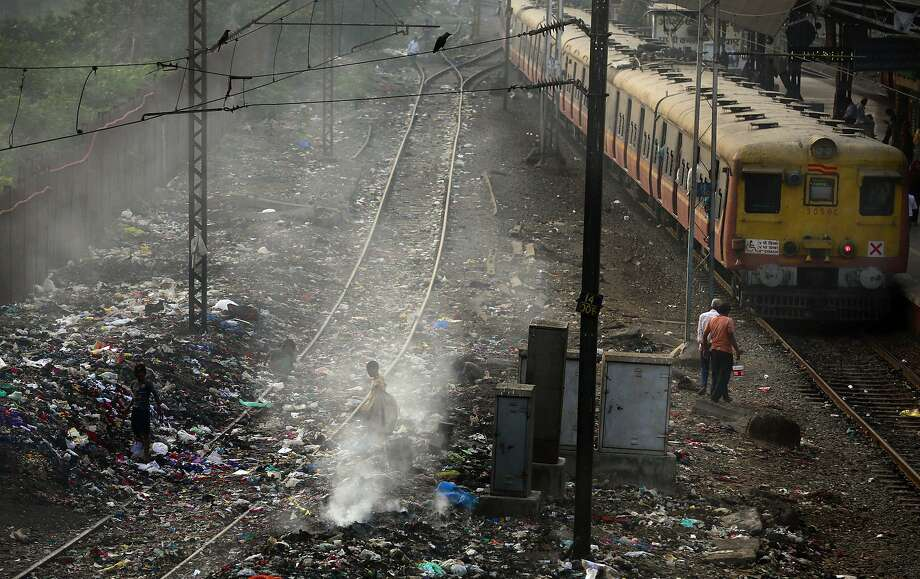 FILE – In this Monday, Jan 26, 2015 file photo, a local train moves past burning garbage at a local train station in Mumbai, India. The World Health Organization on Thursday May 12, 2016 released new information from its Global Urban Ambient Air Pollution Database, that says 98 percent of residents in large cities of low- and middle-income countries are facing excessively high air pollution. (AP Photo/Rafiq Maqbool, File) Photo: Rafiq Maqbool, Associated Press