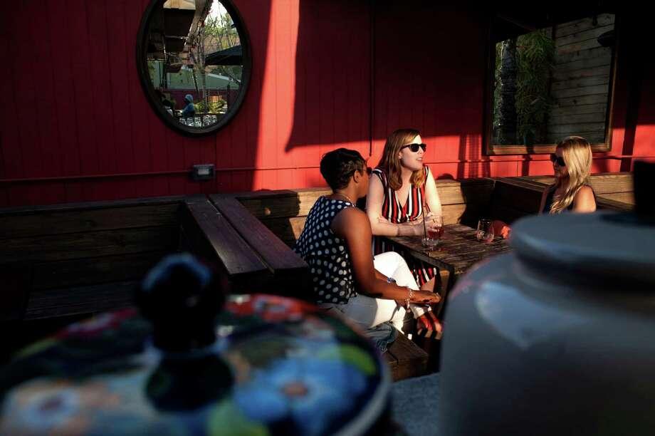 Friends soak up the last of the afternoon sun on Boheme's patio. Photo: Spike Johnson, Freelance / Houston Chronicle