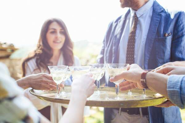 Man holding tray of drinks, group of friends reaching for drinks champagne sparking wine