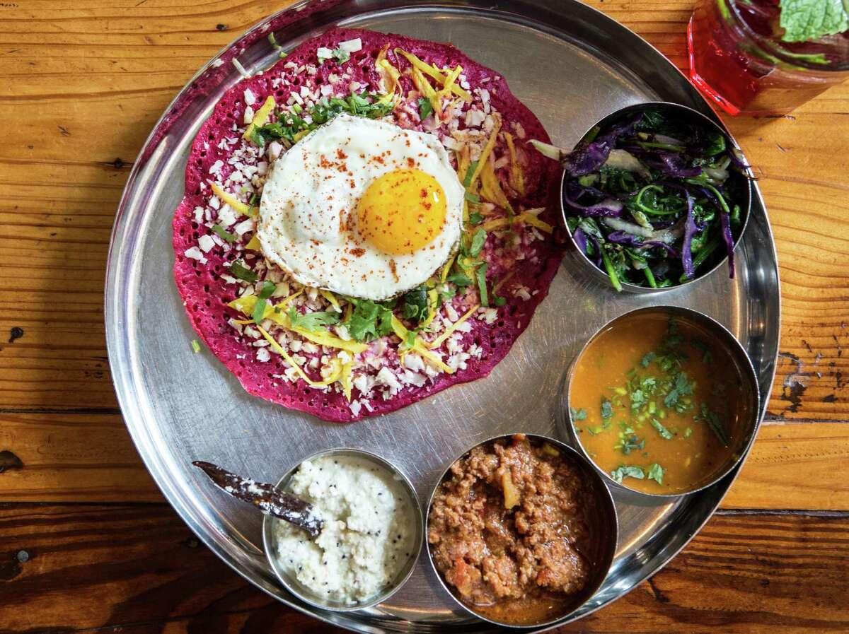Pondicheri's beet uttapum is a flat thick dosa with ginger and fresh coconut fried egg accompanied with keema, sautéed greens, sambhar and coconut chutney.