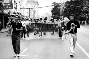 Cadets hold the university's mascot, a rattlesnake, as the band marches through downtown for the Battle of Flowers Parade in the 1960s.
