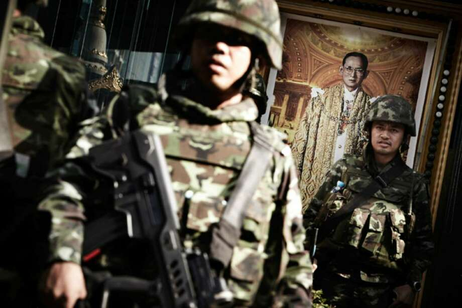 BANGKOK, THAILAND - APRIL 19: Thai army soldiers stand alert next to the picture of Thai King Bhumibol Adulyadej  at Bangkok's Silom district as Red shirt supporters of ousted premier Thaksin Shinawatra threaten to take their protest to the financial district of Bangkok on April 19, 2010 in Bangkok, Thailand. The army have vowed not to let the protestors move, whilst the anti-Thaksin yellow shirt PAD protestors gave the government a week to end the crisis or claimed they would take matters into their own hands.  (Photo by Athit Perawongmetha/Getty Images) Photo: Athit Perawongmetha, Getty Images / 2010 Getty Images