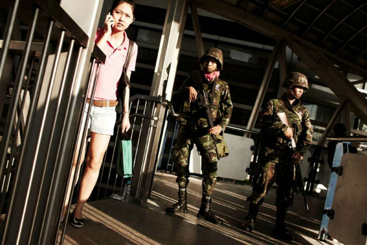 BANGKOK, THAILAND - APRIL 19: A pedestrains walks past Thai army soldiers securing securing the walkway of a skytrain station in Bangkok's Silom district as Red shirt supporters of ousted premier Thaksin Shinawatra threaten to take their protest to the financial district of Bangkok on April 19, 2010 in Bangkok, Thailand. The army have vowed not to let the protestors move, whilst the anti-Thaksin yellow shirt PAD protestors gave the government a week to end the crisis or claimed they would take matters into their own hands. (Photo by Athit Perawongmetha/Getty Images)