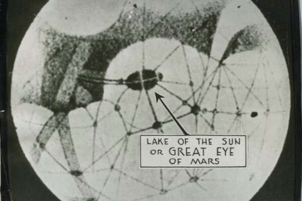 """July 22, 1939 caption read: """"Plant life on Mars?... Inverted as seen through an astronomical telescope, this drawing of Mars shows the Lake of the Sun, which according to color photographs, has changed its shape and is dark blue and green. The photo, made in South Africa by Earl Slipher, American, aparently proves the presence of plant life on Mars. Hurtling through space, the baleful ruddy-colored planet rapidly is coming closer to Earth than at any time in the last 15 years. Its spatial path is destined to bring Mars to within 36,030,000 miles of the Earth -- a moment for which the astronomical world breathlessly awaits."""" International News Photos."""