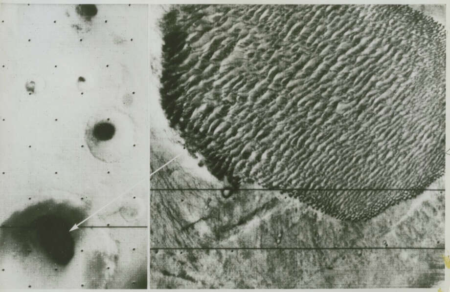 "Original NASA caption reads: ""At right is a, 80-by-40-mile dune field in the floor of a 93-mile-wide crater in the Hellespont retion of Mars. The dune field appears as a black spot, at left, in a wide-angle photograph of the crater (arrow). The similarity of size and direction of the individual dunes indicates they were formed by strong winds blowing from the same direction, which in this case is from the southwest. Mariner 9 has been in Martion orbit since Nov. 13, 1971, has returned 6,824 photographs, and has mapped 85 percent of Mars. The straight dark lines across the pictures are missing lines of picture data which can be restored by computer process."" Photo dated June 25, 1972. Photo: NASA"