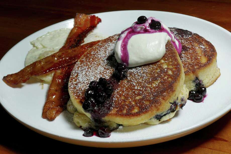 Blueberry pancakes include housemade compote and are served with two eggs and a choice of bacon or sausage. Photo: Billy Calzada /San Antonio Express-News / San Antonio Express-News
