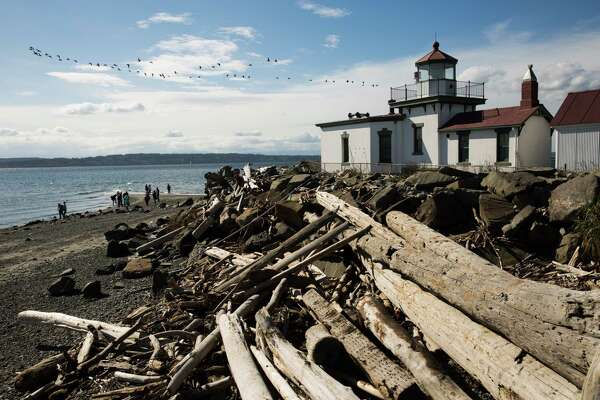 People explore around the Discovery Park lighthouse, the West Point Light, in Seattle on April 14, 2016.