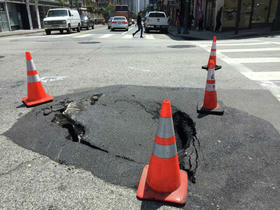 A sinkhole on Polk and Post streets in San Francisco was cordoned off by emergency cones Thursday. The crater formed just three days after gaping sinkhole measuring 12 feet by 5 feet opened up on Mission Street between New Montgomery and Second streets. Photo: Kimberly Veklerov / The Chronicle / /