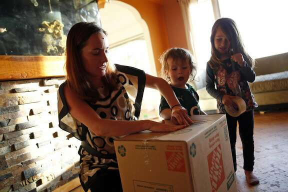 Kelly Dwyer tapes a box as her daughter, Saoirse, 5, and son, Cianan, 18 months, watch her prepare to move out of her family's residence in San Francisco, Calif., on Wednesday, June 24, 2015.