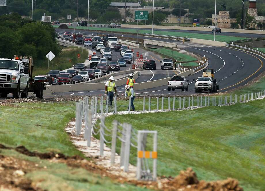 Construction crews finish off the remainder of work needed along the northbound lanes of Loop 1604 as officials marked the re-opening of 1604 between Culebra and Bandera roads with a ceremony on Thursday, May 12, 2016. In March 2014, the $82 million project kicked off to relieve traffic congestion on the Northwest portion of the county - one of the fastest growing area according to Texas Transportation Commissioner Bruce Bugg. The work created four express lanes for drivers in hopes of cutting travel times in half, Bugg said. The new section of 1604 was expected to be open by Thursday afternoon. (Kin Man Hui/San Antonio Express-News) Photo: Kin Man Hui, Staff / San Antonio Express-News / ©2016 San Antonio Express-News